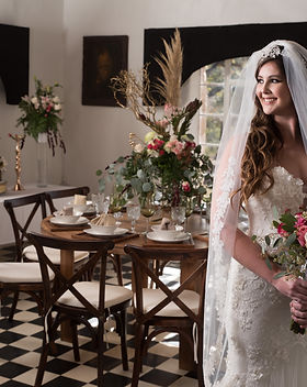 Tuscany Venue bride smiling with bouquet in the foyer.