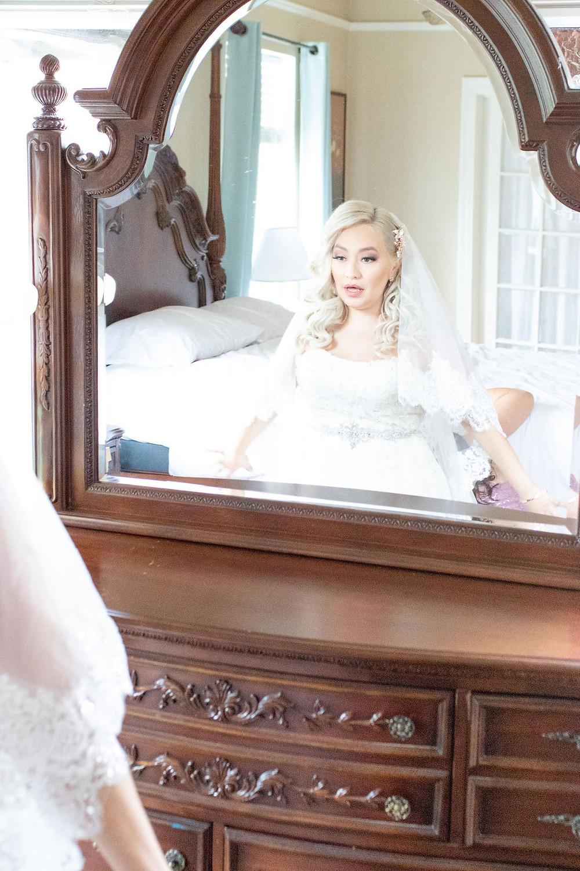 San Antonio Bride looks in the mirror in her wedding dress