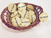 """Brown basket, full of yellow buttons, black text saying """"Be Open""""."""