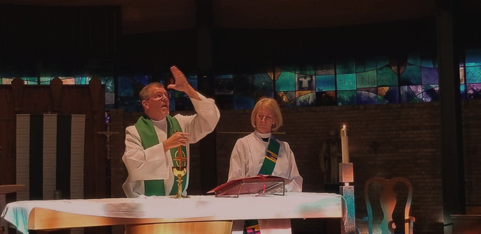 Rev Richard Mahaffy officiating Eucharist while Deacon Suzanne stand by