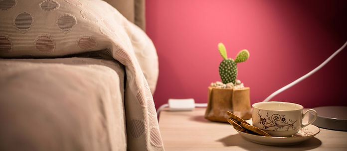 Particolare del letto e del comodino. Lampada accesa, piccolo vaso con cactus, tazza da té e biscotti