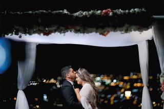 זוג חתן וכלה בחופה על רקע חומות העיר העתיקה בירושלים. צילום - ליאור משה