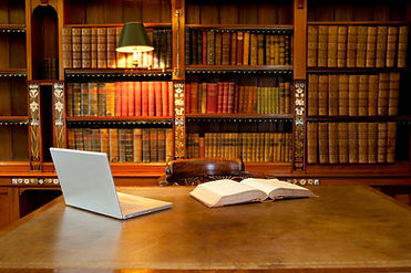 Laptop and book lying on a desk in class
