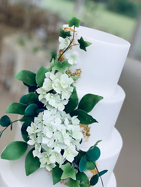 white wedding cake with sugar flowers and foliage