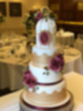 Winter wedding cake in gold and burgundy.