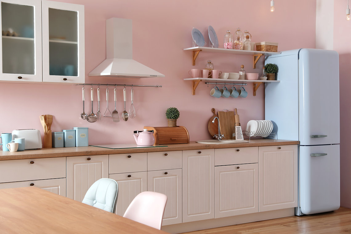 Stylish pink kitchen interior with dinin