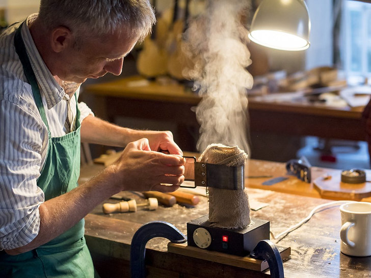 Mark Jennings violin maker bending ribs for violin.   Photo by Miles Essex. IMS Prussia Cove.