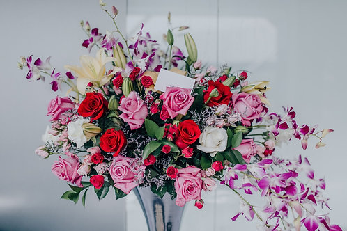 table arrangement of Mixed roses orchids and lilys
