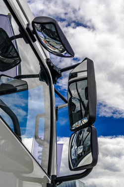 Rear view mirrors against a blue sky