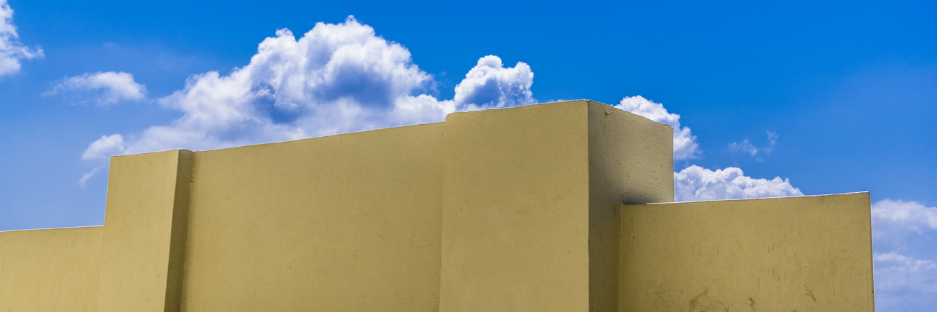 Blue sky above yellow wall
