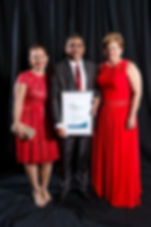 Two ladies in red evening dresses,and a man in a grey suit and red tie, holding a framed award certificate
