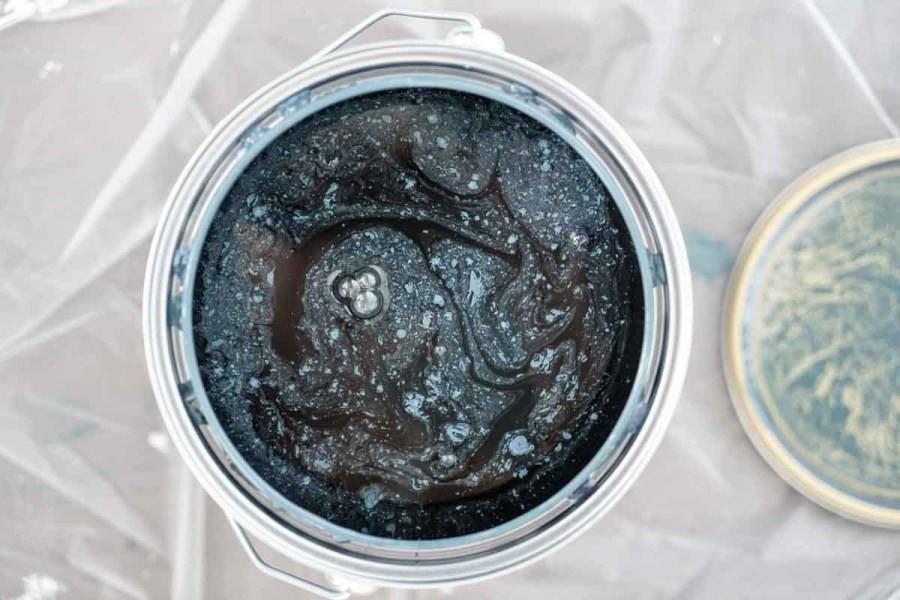 De verf voordat het geroerd is, je ziet de blauwe pigmenten