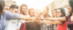 Young happy people stacking hands outdoo