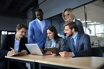 brainstorm-group-business-people-looking-laptop-together-one-business-woman-looking-camera