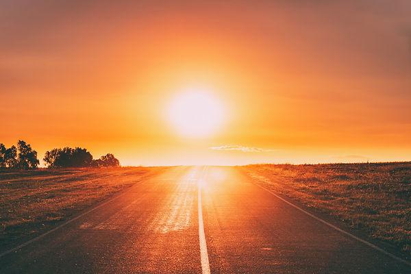 sun-rising-above-asphalt-country-open-ro