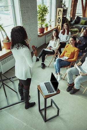 female-african-american-speaker-giving-presentation-hall-university-workshop.jpg