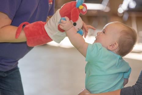 A little girl enjoying exploring Maggie Moo the puppet.