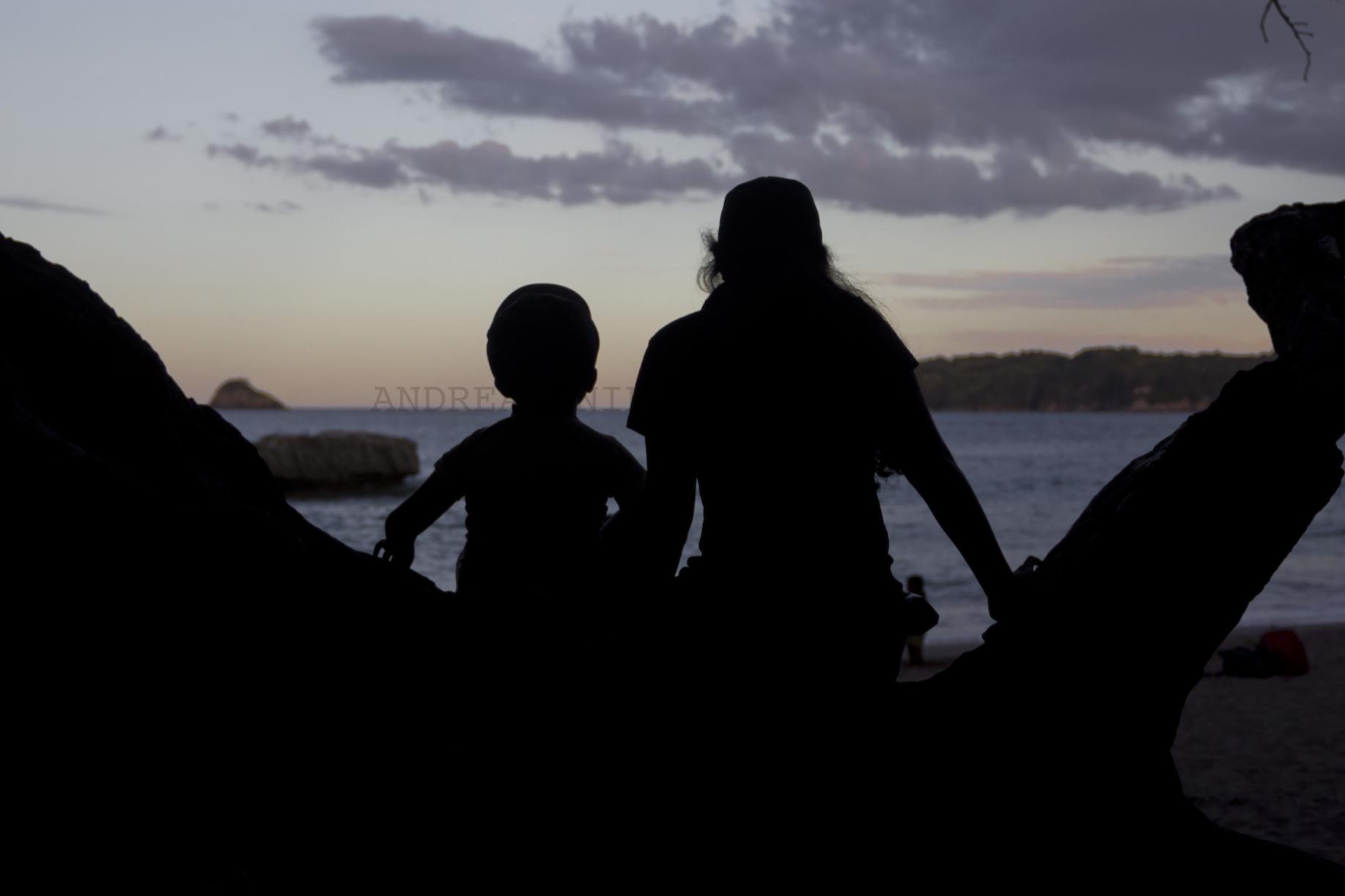 Kvinde og barn nyder solnedgang.