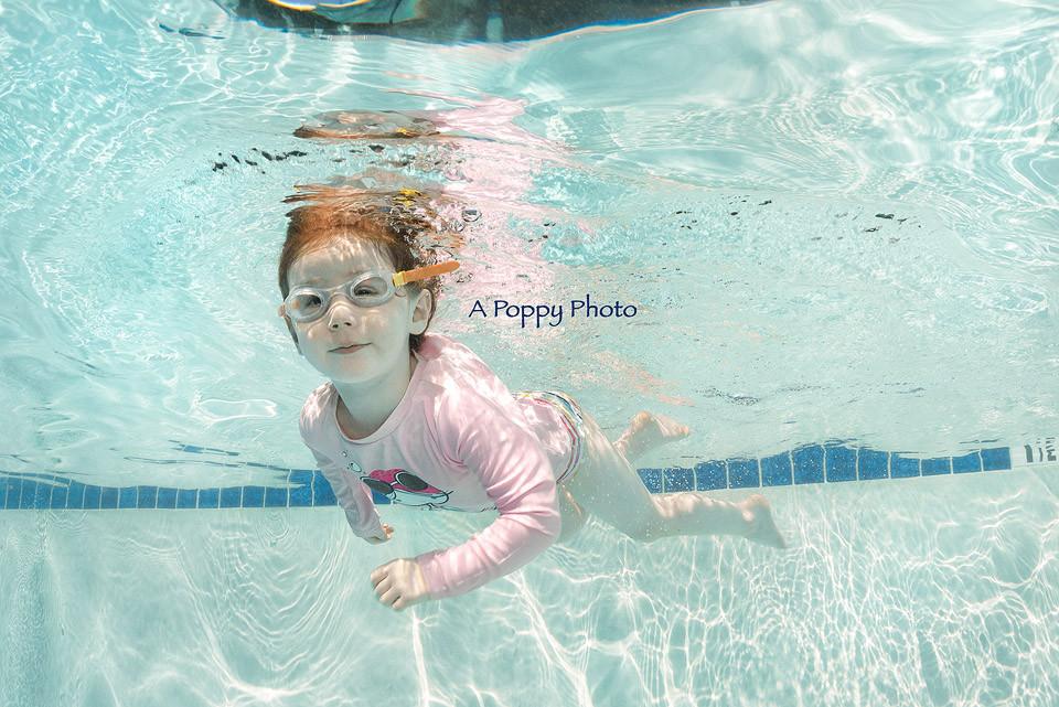 Underwater image of girl in a pink rash guard swimming at Makai Swim School