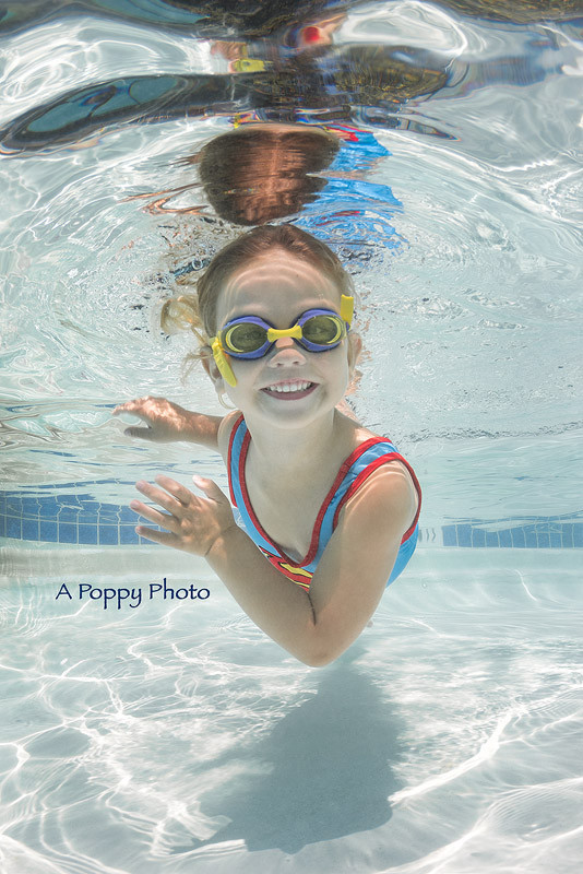 Underwater image of little girl in Supergirl swimsuit smiling