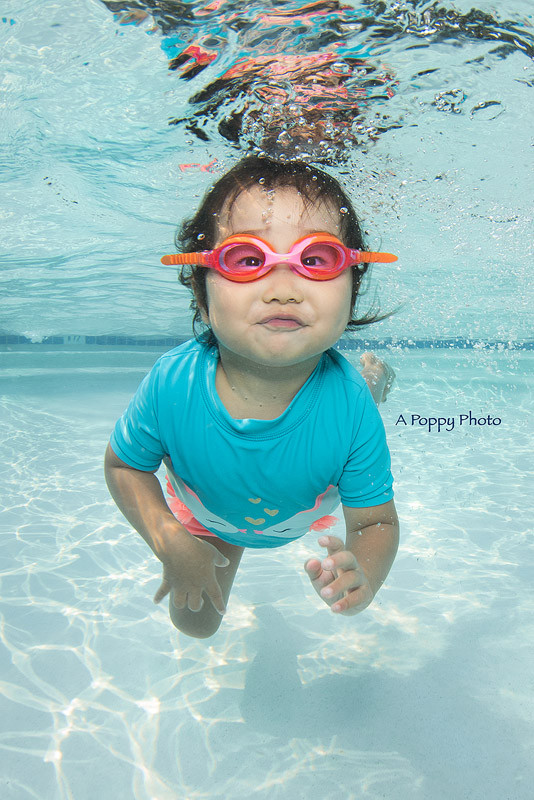 Underwater image of little girl in pink goggles and blue rash guard swimming
