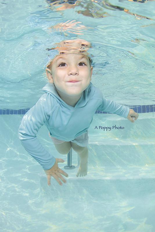 Underwater image of boy in blue rash guard smiling