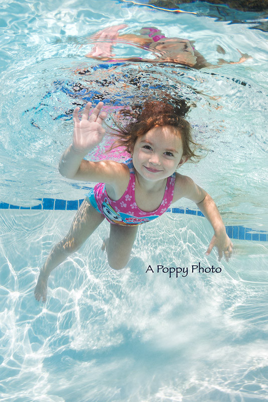 Underwater image of girl in pink Paw Patrol swimsuit smiling and waiving