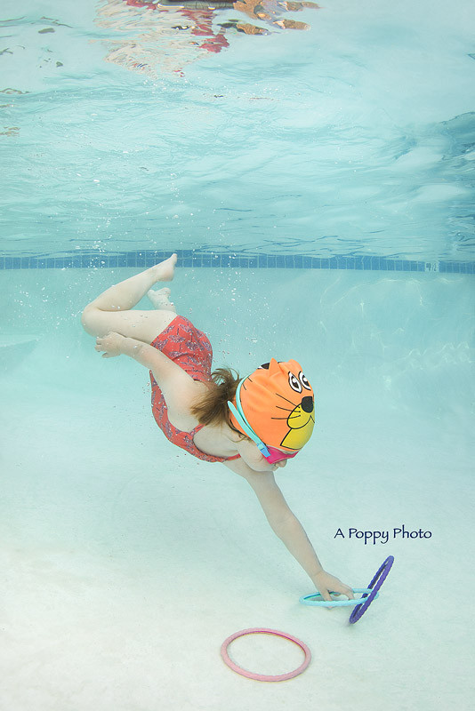 Underwater photography image of girl in tiger swim cap diving for rings at the bottom of the pool