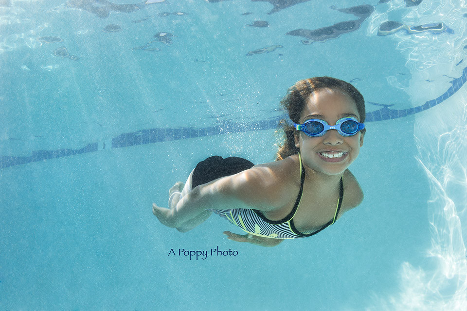 Underwater image of girl in blue goggles smiling