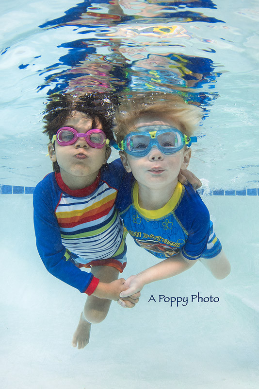 Underwater image of little boy and little girl hugging