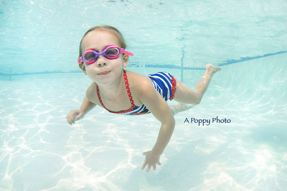Underwater image of girl swimming in a red white and blue