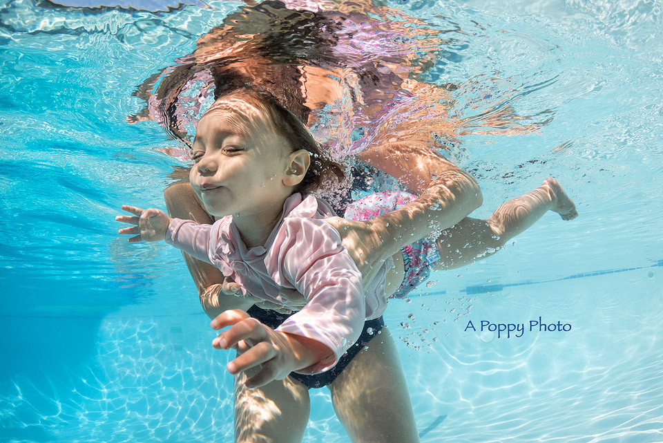 Underwater photography image of little girl swimming in a pink swim school in a baby swim class with mom
