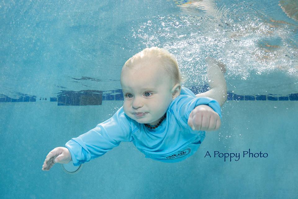 Underwater image of baby boy in blue rash guard going underwater at Makai Swim School