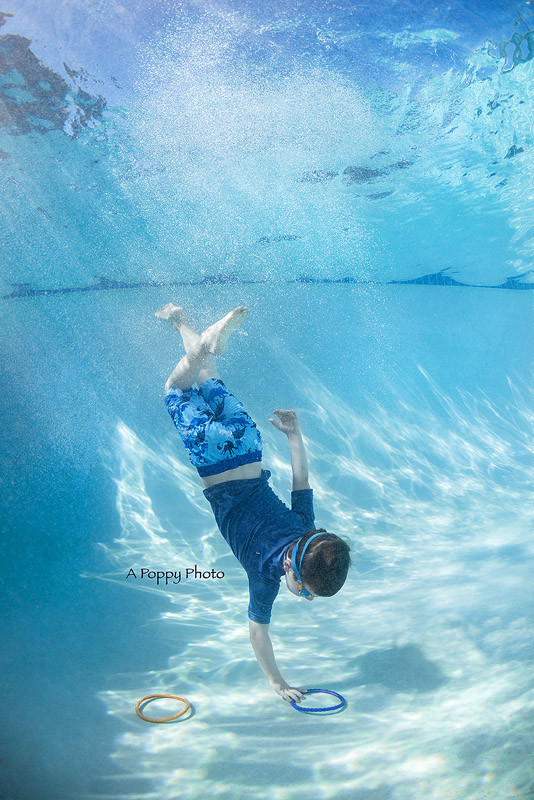 Underwater image of boy in blue swimsuit swimming to the bottom of the pool to get rings