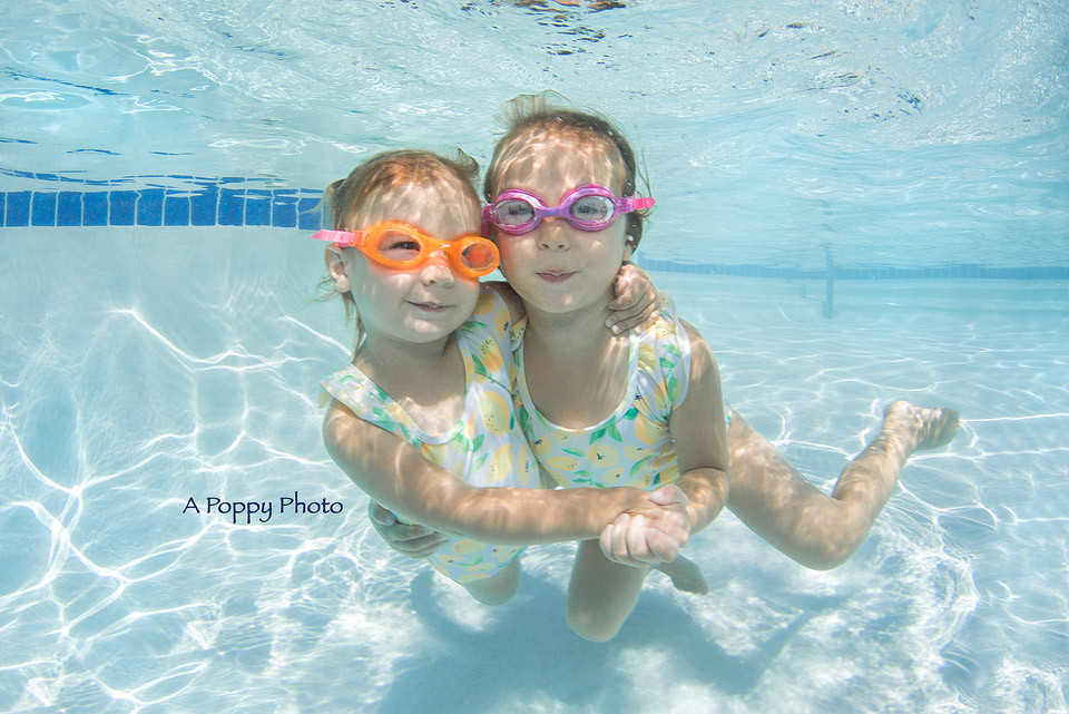 Underwater image of two sisters in matching lemon swimsuits hugging and swimming together