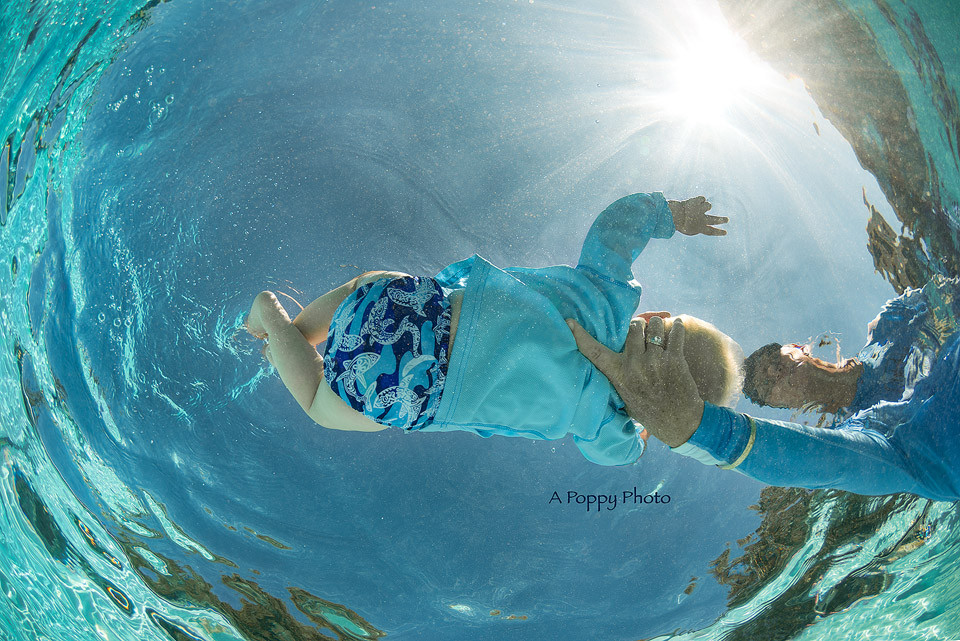 Underwater image of baby doing a back float giving a peace sign