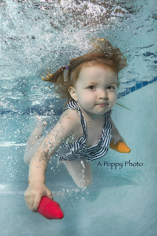 Underwater image of toddler girl swimming with pool chalk