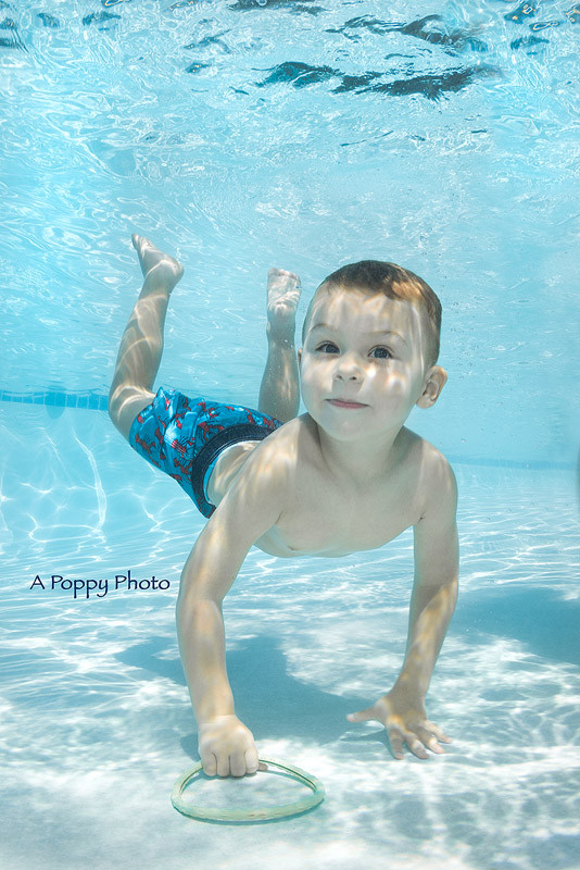 Underwater photography image of boy diving for rings in pool