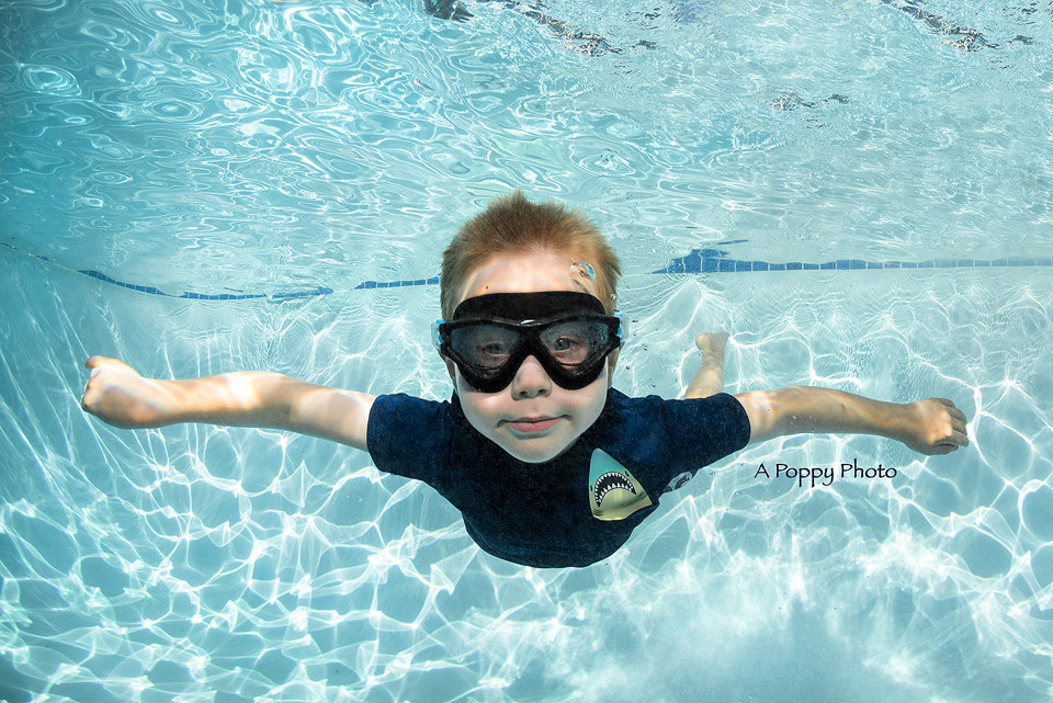 Underwater photography image of boy swimming with black goggles and a shark rash guard at Makai Swim School