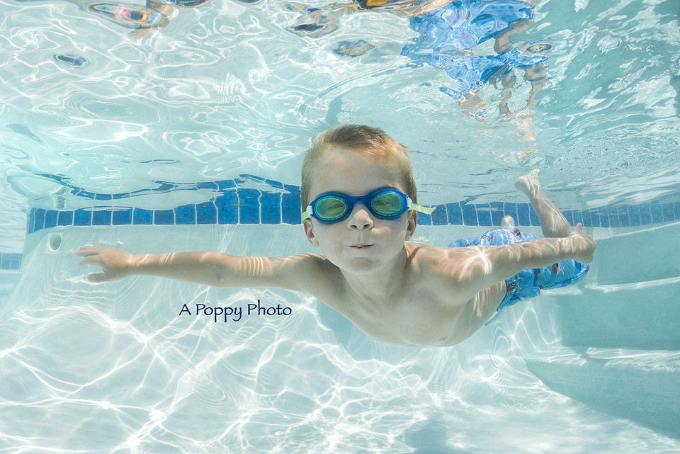 Underwater image of boy in blue goggles swimming
