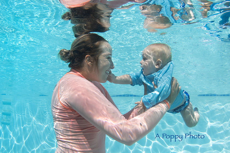 Underwater photography image of mom and baby boy underwater with baby touching mom's face