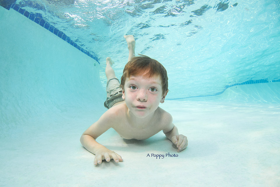 Underwater image of boy laying on the bottom of the pool at Makai Swim School