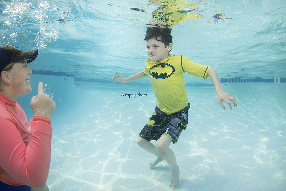 Underwater photography image of a swim instructor showing a child in a batman swimsuit how to smile underwater