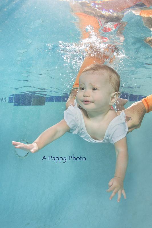 Underwater image of baby girl in white swimsuit going underwater during a baby swimming class at Makai Swim School