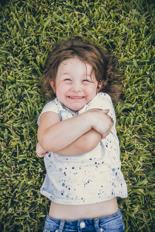 Smiling girl laying on backyard grass Tampa