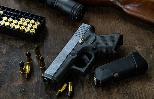 Glock Junie - Glock Pistol with Magazine and ammunition laying on wood table