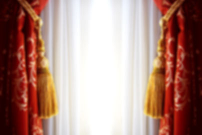 Beautiul red curtains held open with gold ties.