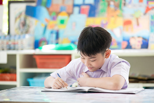 happy-asian-child-writing-book-with-smil
