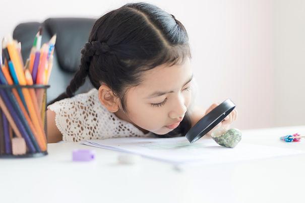 little-asian-girl-using-magnifier-doing-