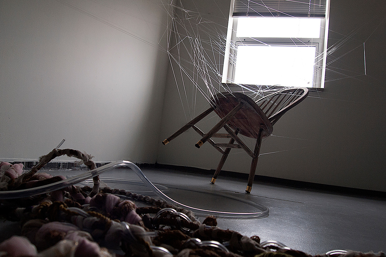 1. The Leftovers, 2018   found chair, fabric from clothes found on the street and medical tubing braided into a rope, elastic threads, gold leaf. 120(l) x 72(w) x 60(h) in.   Site specific installation.